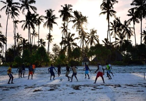 Football players on white sands under tall palm trees